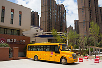 A modern version of a yellow school bus stands outside a school in Xian, Shaanxi, China.