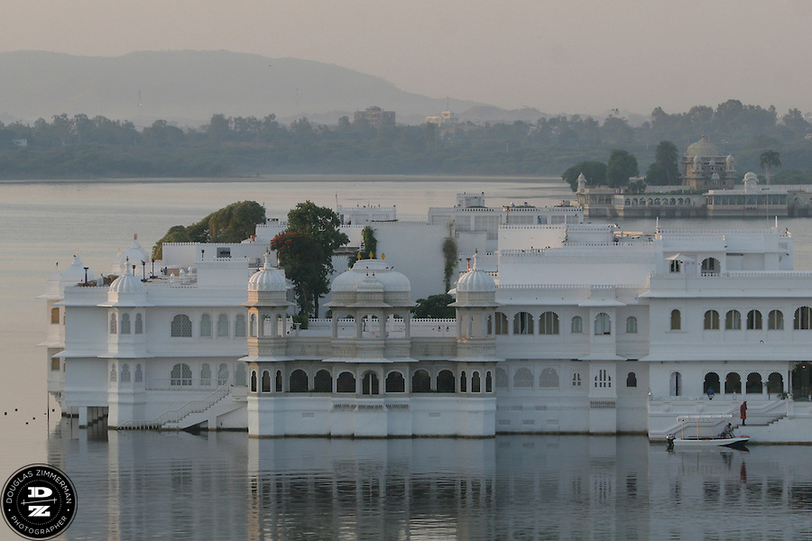 "View of the Lake Palace Hotel, which sits on Jagniwas Island in the center of Pichola Lake, in Udaipur, Rajasthan, India at sunrise.  Udaipur is located in a valley surrounded by the Aravalli hills, and at its center is the Pichola Lake.  The scenic city has been described as ""the most romantic spot on the continent of India"" (by Colonel James Tod).  Photograph by Douglas ZImmerman"