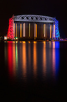 """""""Stars and Stripes - Aerial Lift Bridge""""<br /> After the fireworks ended and crowds left Canal Park, we enjoyed photographing the iconic Aerial Lift Bridge with its vibrant patriotic colors. As luck would have it, the bridge had to lift its lower span to allow passage to the inbound Paul R. Tregurtha (""""thousand footer"""") in the wee hours of the morning. In addition to the beautiful reflection, this long exposure photograph captured the vertical trails created by the lights on the rising lower span. I had envisioned this exact shot for quite some time, and was fortunate to finally have an opportunity to create it as the patriotic bridge welcomed a big laker. I hope you appreciate the uniqueness of this photograph and the spirit of Independence Day."""