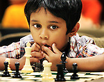 "Sat 17, July 10 (jschess) Photo by Justin Shaw -  Five year old Manish Rangan (cq) considers his next move in a tense chess match at the Cordova Branch Library. The Memphis Chess Club invited teens 12 - 17 years old to the Cordova Branch Library for a chess tournament. ""Manish showed so much enthusiam for the game at an early age"", says father Svresh Rangan (cq). Tony Maneclang, United States Chess Club Federation Tournament Director and Memphis Chess Club Secretary ""didn't think Manish was ready this year, believing that he wouldn't devote all concentration to the game because of his youth, but he picked the game right up."" Maneclang says ""Chess players compare multiple moves. So, kids develop their analytical skills playing the game."" Maneclang adds that improved problem-solving skills are another byproduct of play. ""Finding solutions under time-pressure makes players focus."""
