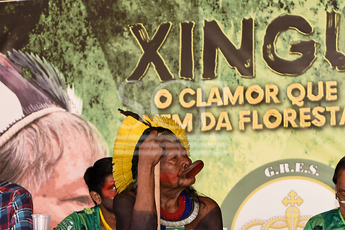 Rio de Janeiro, Brazil. Imperatriz Leopoldinense samba school; preparations for carnival. Chief Raoni Metuktire leans on his borduna war club below a Xingu poster at the pre-carnival press conference.