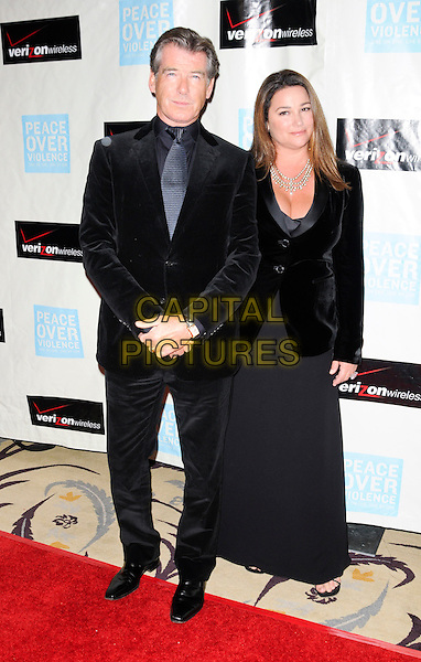 PIERCE BROSNAN & KEELY SHAYE SMITH .arriving at Peace Over Violence's 38th Annual Humanitarian Awards Dinner and Silent Auction held at the Beverly Hills Hotel in Beverly Hills, California, USA, November 6th 2009..full length married couple black velvet jacket cleavage keeley husband wife suit long maxi skirt dress  .CAP/ROT.©Lee Roth/Capital Pictures