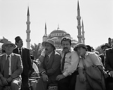 TURKEY, Istanbul, actors sitting together with mosque in the background (B&W)