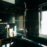 A stylish dark green marble-tiled bathroom