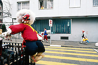 "Switzerland. Basel. Fasnacht Carnival. An old woman looks out of her apartment's window musicians from a ""Clique"" walking on the road's pavement. A  ""Clique"" is a group of persons playing music in the streets during the three days of the Fasnacht Carnival. A masked figure is tied on a wood fence.  © 1997 Didier Ruef"