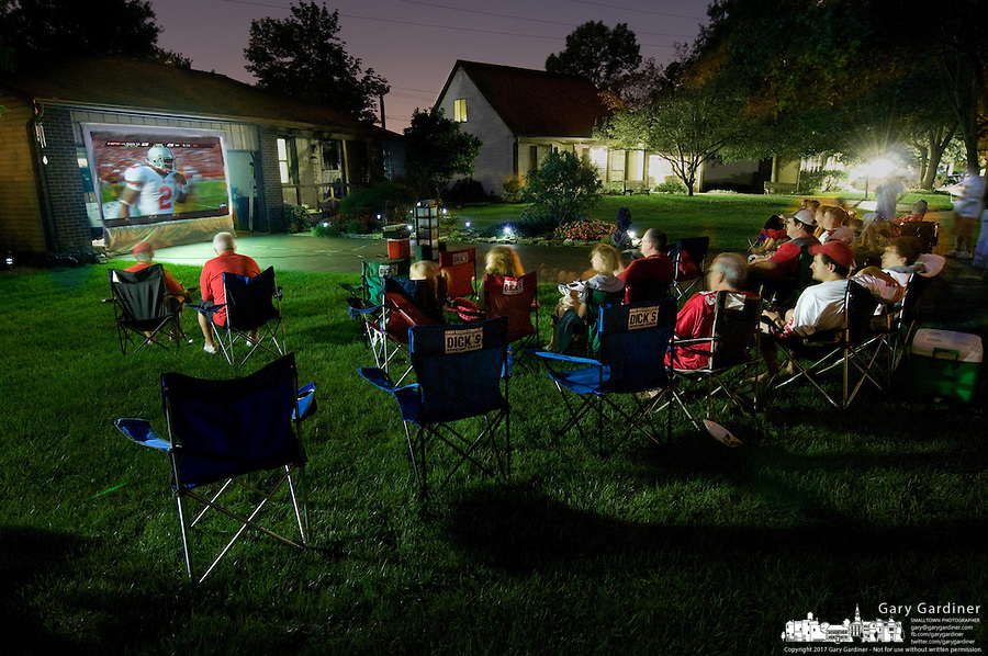 Neighbors gather in a front yard of a Westerville, Ohio, home to watch projection broadcast of an Ohio State Buckeyes football away game.  Photo Copyright Gary Gardiner.