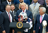 United States President Donald J. Trump, center, hold up the helmet he received from New England Patriots head coach Bill Belichick, left, during the ceremony welcoming the Super Bowl Champions to the South Lawn of White House in Washington, DC on Wednesday, April 19, 2917.  Team owner Robert Kraft looks on from right.<br /> Credit: Ron Sachs / CNP<br /> (RESTRICTION: NO New York or New Jersey Newspapers or newspapers within a 75 mile radius of New York City)