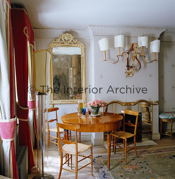 A theatrical wall sconce hangs above a mirrored fireplace and small Biedermeier dining table in a corner of the living room