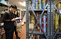 NWA Democrat-Gazette/DAVID GOTTSCHALK Johnny Down (left), a sophomore at the University of Arkansas, volunteers with his sister Jenny, a junior, Thursday, February 7, 2019, fill an order for a client at the Jane B Gearhart Full Circle Food Pantry on the campus in Fayetteville. The pantry celebrated a grand reopening Thursday following a remodel that increased its storage capacity by 40 percent and the eighth year anniversary of the pantry. The student-run program offers assistance to students, faculty, staff and their families who are facing food insecurity or in need of supplemental food.