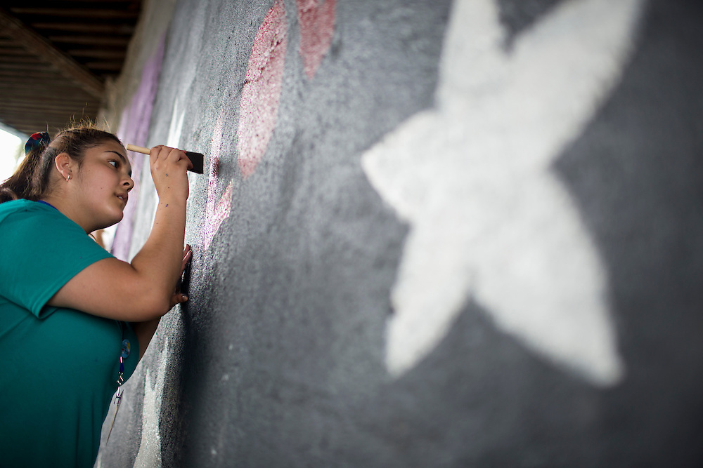 """Erica Meneses works on a mural beneath a train bridge during """"Circle the City with Service,"""" the Kiwanis Circle K International's 2015 Large Scale Service Project, on Wednesday, June 24, 2015, in Indianapolis. (Photo by James Brosher)"""