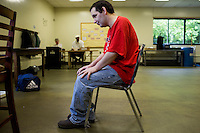 Michael Martin waits for assistant and caretaker Gilbert Helas (green shirt) to prepare more documents for him to shred at work at Site 7 at the Fernald Developmental Center in Waltham, Massachusetts, USA.  Michael, 52, cannot speak. Some of the residents perform menial tasks for pay.