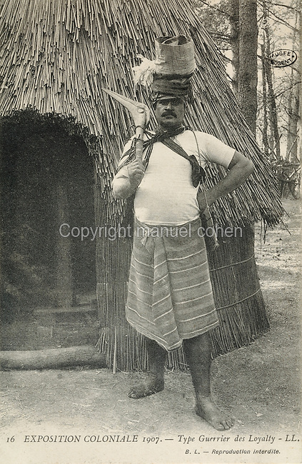 Warrior outside a traditional thatched hut, from the Loyalty Islands in New Caledonia, at the Colonial Exhibition of 1907, held in the Jardin d'Agronomie Tropicale, or Garden of Tropical Agronomy, in the Bois de Vincennes in the 12th arrondissement of Paris, postcard from the nearby Musee de Nogent sur Marne, France. The garden was first established in 1899 to conduct agronomical experiments on plants of French colonies. In 1907 it was the site of the Colonial Exhibition and many pavilions were built or relocated here. The garden has since become neglected and many structures overgrown, damaged or destroyed, with most of the tropical vegetation disappeared. The site is listed as a historic monument. Picture by Manuel Cohen / Musee de Nogent sur Marne
