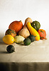A collection of vegetables including pumpkin, squash and lemons on a beige linen table cloth.