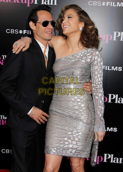 "MARC ANTHONY & JENNIFER LOPEZ .""The Back-up Plan"" Los Angeles Premiere held at the Regency Village Theatre, Westwood, California, USA, 21st April 2010. .arrivals half length sleeve one shoulder silver sheer shimmery shiny dress black suit married husband wife arm around smiling couple sunglasses clutch bag  .CAP/ADM/MJ.©Michael Jade/AdMedia/Capital Pictures."