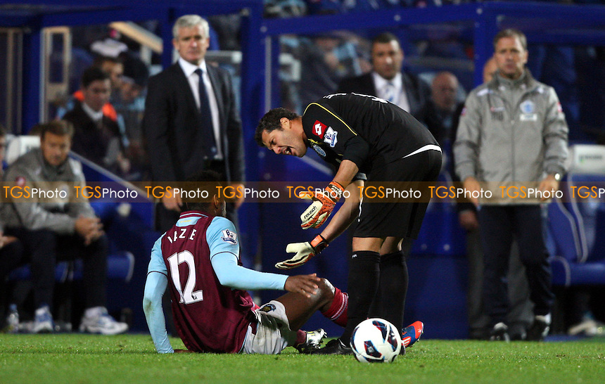 Ricardo Vaz Te of West Ham is down injured and Julio Cesar of QPR tries to get him to his feet - Queens Park Rangers vs West Ham United - Barclays Premier League at Loftus Road, London - 01/10/12 - MANDATORY CREDIT: Rob Newell/TGSPHOTO - Self billing applies where appropriate - 0845 094 6026 - contact@tgsphoto.co.uk - NO UNPAID USE.
