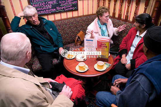 Group of older people chatting over a cup of coffee in a pub,
