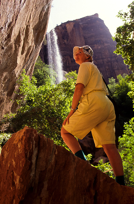 Female hiker by Emerald Pool waterfall in eroded sand stone mountains and canyons in Zion National Park, Utah, USA