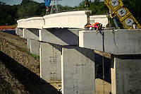 A worker helps a crane operator by guiding a concrete beam into place on a bridge being constructed. Construction worker.