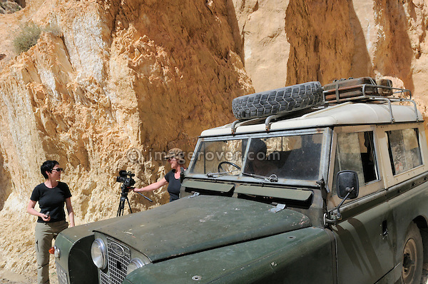 Africa, Tunisia, nr. Saket. Desert travellers Heike and Kerstin setting the video camera up to film in the famous narrow gorge south of Saket. --- No releases available, but releases may not be needed for certain uses. Automotive trademarks are the property of the trademark holder, authorization may be needed for some uses.  --- Info: Image belongs to a series of photographs taken on a journey to southern Tunisia in North Africa in October 2010. The trip was undertaken by 10 people driving 5 historic Series Land Rover vehicles from the 1960's and 1970's. Most of the journey's time was spent in the Sahara desert, especially in the area around Douz, Tembaine, Ksar Ghilane on the eastern edge of the Grand Erg Oriental.