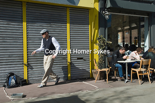 Hackney, Chatsworth Street, man doing street dance, people enjoung Sunday moring cup of coffee. London UK