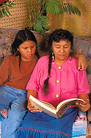 American Indian grandma and grandson ages 65 and 12 reading book.  Minneapolis Minnesota USA