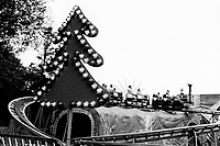 "Switzerland. Canton Zürich. Zürich. People enjoy a roller coaster ride during the traditional ""Knabenschiessen""  (Boys' shooting) festivity held every September in Zürich. A fake swiss mountain landscape and a fir with electric bulbs.10.09.2016 © 2016 Didier Ruef"