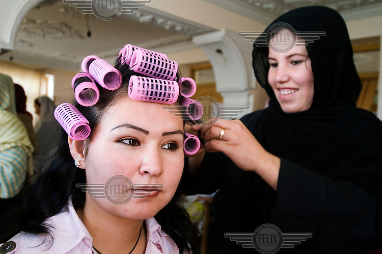 Zahera Mohamadi does the hair of 18 year old Arizu Hayden at the beauty school run by VTAWP (Vocational Training for Afghan Women Programme).