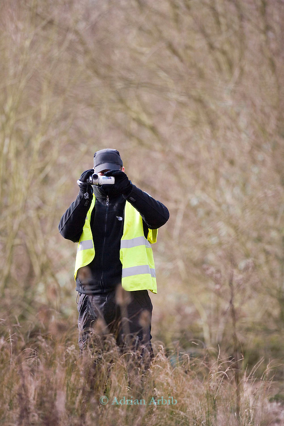 Security guard filiming the photographer.<br /> N Ppwer were  cutting  down  trees and vegetation  at Radley Lakes.  The lake is currently being considered for  town green status and the current work being done is potentially illegal.
