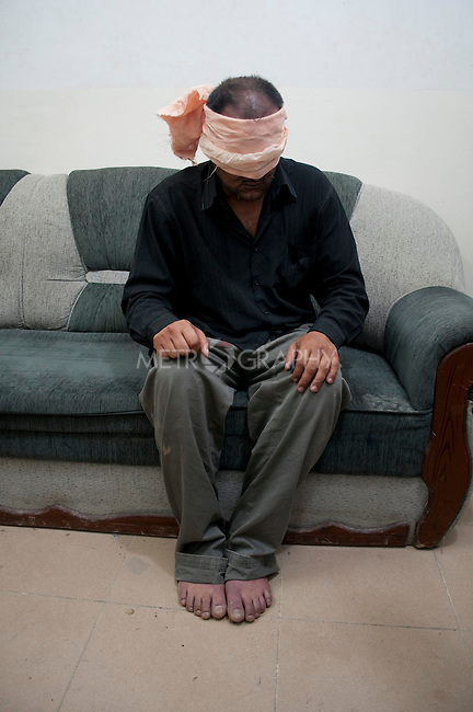 KIRKUK, IRAQ:  An Arab man from the Hai Askari neighborhood of Kirkuk awaits interrogation on the eve of the Iraqi Parliamentary Elections.  The man is suspected of planting a roadside bomb on March 4th that wounded 6 people.