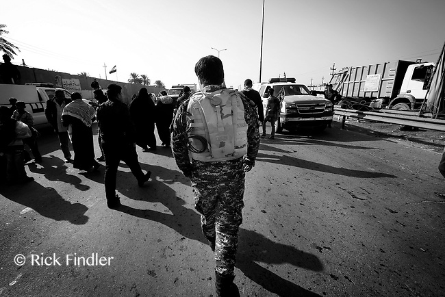 A member of The Hawks walks through a crowd toward the scene where a suicide bomber had detonated his vest, killing 10.