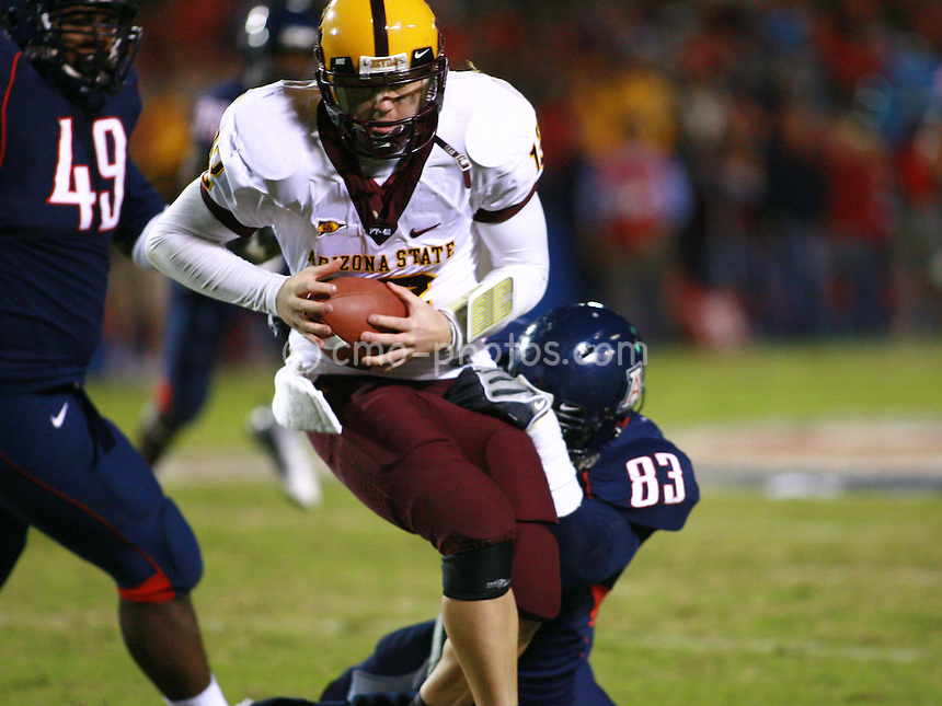 Dec 6, 2008; Tucson, AZ, USA; Arizona State Sun Devils quarterback Rudy Carpenter (12) is pulled down by Arizona Wildcats defensive end D'Aundre Reed (83) in the fourth quarter of a game at Arizona Stadium.  Arizona won the game 31-10.