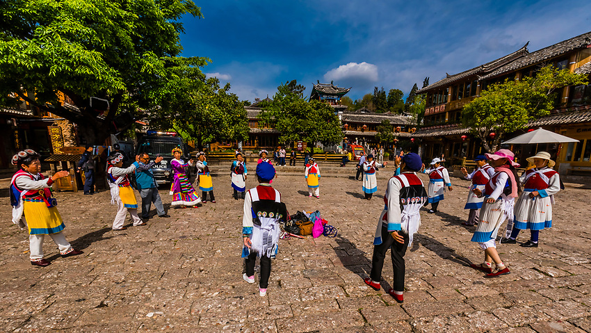 Women of the Naxi ethnic minority dancing in the Old Town (Dayan) of Lijiang, Yunnan Province, China. The Old Town is a UNESCO World Heritage Site.