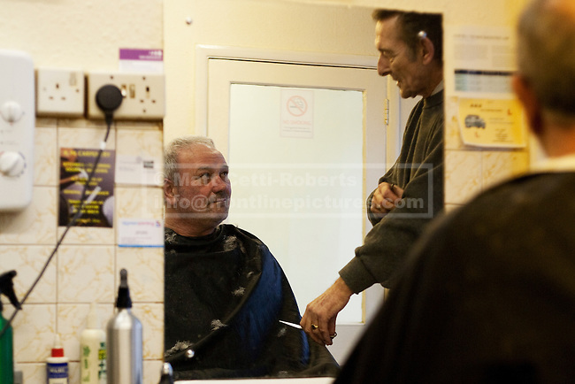 A customer listens as Mike pauses mid-haircut, to give advice on a problem they are discussing.