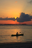 Sunset over kayaker at Wakatobi Dive Resort, Southeast Sulawesi, Indonesia.