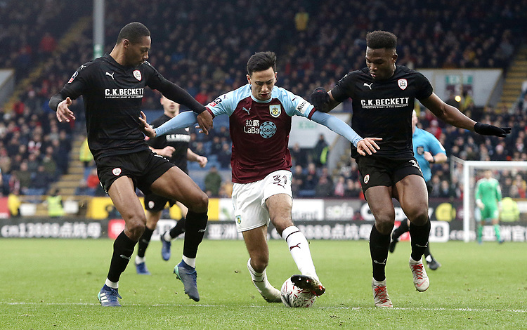 Burnley's Dwight McNeil holds off the challenge from Barnsley's Ethan Pinnock (left) and Dimitri Cavare<br /> <br /> Photographer Rich Linley/CameraSport<br /> <br /> Emirates FA Cup Third Round - Burnley v Barnsley - Saturday 5th January 2019 - Turf Moor - Burnley<br />  <br /> World Copyright © 2019 CameraSport. All rights reserved. 43 Linden Ave. Countesthorpe. Leicester. England. LE8 5PG - Tel: +44 (0) 116 277 4147 - admin@camerasport.com - www.camerasport.com