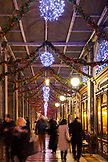 ITALY, Venice. Christmas decorations hangs along the crowded Procuratie Nuove in St. Mark's Square. Caffe Florian is on the right wth some chairs and tables in front of the windows.