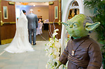 WATERBURY, CT-081217JS05-- Bride, Francheska Lopez, is escorted into the ceremony by her brother Jose, as Yoda looks on, during their Star Wars themed wedding Saturday at the community room at Holy Trinity Church in Waterbury. <br />  Jim Shannon Republican-American