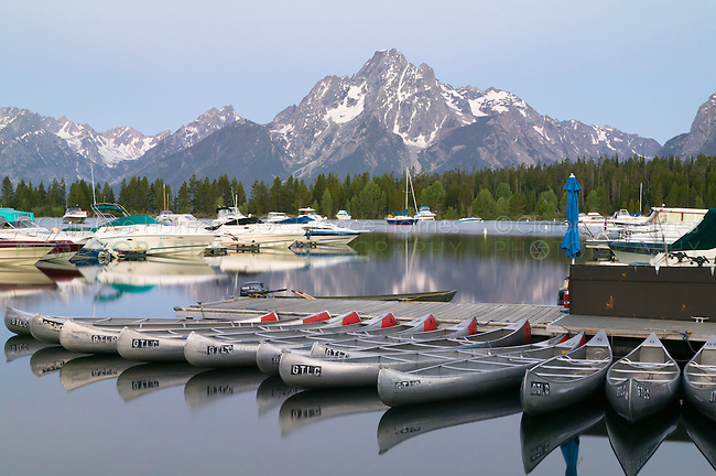 The cool light prior to sunrise on Mount Moran and the still surface of Jackson Lake and Colter Bay, full of sleeping boats and canoes.  Grand Teton National Park, Wyoming, USA