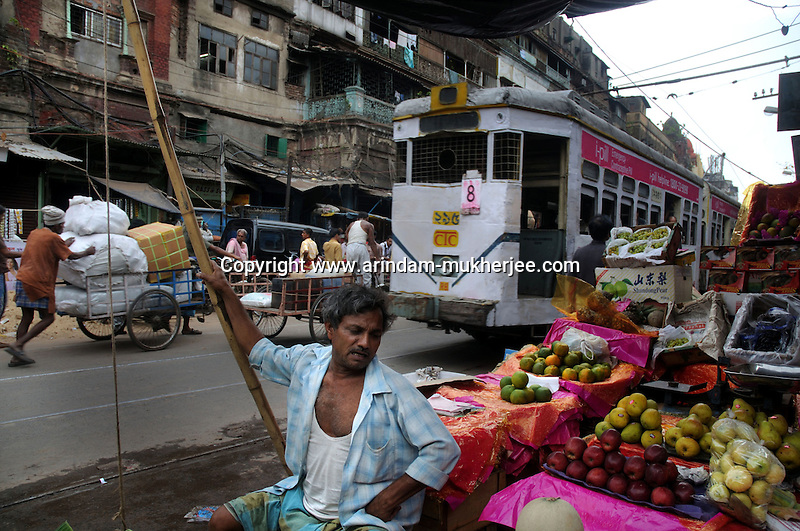 A fruit seller on a street in old Calcutta while a tram passes by. Calcutta is the only city in India where tram service is still available.