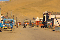 The main street in Tingri China and Chinese trucks passing through.