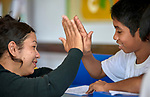 Dora Nilde Andrade da Silva (left) exchanges a high five with Joelson Souza da Costa, 12, in a tutoring program sponsored by the Catholic Church in Atalaia do Norte in Brazil's Amazon region. The program helps kids keep up with their school work. Andrade is a volunteer.<br /> <br /> Written parental consent obtained.