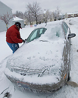 Lisa Rubinow scrapes ice from the windshield of her car as she prepares to go to work in Westerville, Ohio, Thursday, December 23, 2004. A winter storm covered central Ohio with as much as a foot of snow and an inch of ice forcing school and business closings.