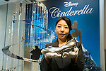 A member of staff shows a platinum Cinderella high heel next to the ''Disney Cinderella Platinum Christmas Tree'' at the Ginza Tanaka jewelry store in Ginza, on November 19, 2015, Tokyo, Japan. This year's tree is decorated with Cinderella movie characters and includes a 3 carat diamond on Cinderella's high heel. The tree is 2.5m in height and weighs approximately 9kg and is valued at approximately 100,000,000 JPY (809,667.44 USD). (Photo by Rodrigo Reyes Marin/AFLO)