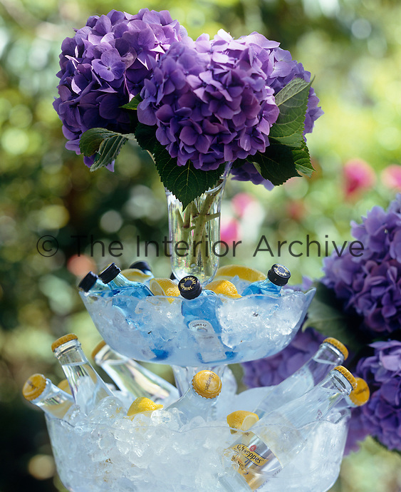 A two tiered glass stand filled with ice and mini gin and tonic bottles makes a self-service bar for an alfresco summer lunch