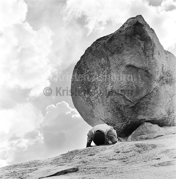 A young girl prays beneath a rock, Mbvuku, Zimbabwe, March, 2002