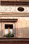 Looking up at a building covered in faded frescos in Mantua, Italy.