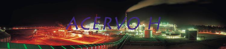 Foto panorâmica da alunorte feita em 1996.<br /> <br /> Alunorte, a maior refinaria de alumina do mundo Em 1978, um acordo entre os governos do Brasil e do Japão — que contou com a participação da Vale (na época, chamada de Companhia Vale do Rio Doce) — criou a empresa Alunorte - Alumina do Norte do Brasil S.A, idealizada para integrar a cadeia produtiva do alumínio no Pará, estado rico em bauxita, matéria-prima da alumina.Construída estrategicamente em Barcarena, município situado a 40 quilômetros, em linha reta, de Belém (PA), a Alunorte iniciou suas operações em julho de 1995, após um período de paralisação das obras em função de uma crise no mercado, que retardou a implantação do projeto.Em 2000, iniciou-se o primeiro projeto de expansão da refinaria, que foi concluído em 2003. Com a ampliação, a capacidade produtiva passou de 1,6 para 2,5 milhões de toneladas de alumina por ano. Com esse salto na produção, a empresa ganhou destaque no cenário internacional e passou a figurar como a maior refinaria da América Latina e a quarta do mundo. Nesse mesmo ano, iniciou-se a segunda expansão.A conclusão da segunda expansão terminou no primeiro semestre de 2006, consolidando a Alunorte como a maior refinaria de alumina do planeta. A empresa chegava então a uma capacidade de produção de 4,4 milhões de toneladas de alumina por ano, gerando emprego para cerca de 2,5 mil pessoas (funcionários próprios e contratados).Em agosto de 2008, a Alunorte concluiu as obras da Expansão 3, um investimento de R$ 2,2 bilhões que capacitou a empresa para produzir 6,26 milhões de toneladas de alumina por ano. Com esse patamar, a Alunorte passou a ser responsável por 7% da produção mundial de alumina.Barcarena, Pará, Brasil.Foto: ©Paulo Santos1996