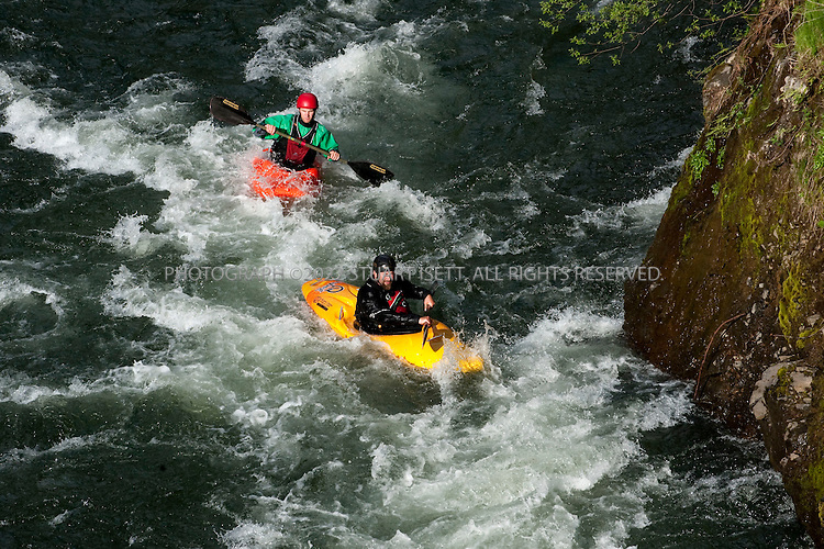 5/18/2009--Sandy, OR, USA..Kayakers Paul Kuthe (front: black helmet, yellow kayak) and Matt Preusch (writer: red helmet, orange kayak) kayak a recently opened stretch of the Sandy River in Oregon. The Marmot Dam was removed from the river in 2007 allowing fish and kayakers to travel the newly opened stretch of water...©2009 Stuart Isett. All rights reserved.