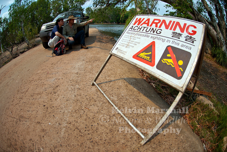 Young couple pointing out a Crocodile as they cross over the river in their vehicle.