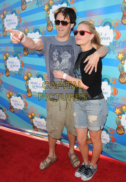 STEPHEN MOYER & ANNA PAQUIN .at the Make-a-Wish Foundation Funday at The Santa Monica Pier in Santa Monica, California, USA, .March 14th, 2010                                                                    .full length sunglasses  black aviators red wayfarers ray bans denim shorts trainers couple black grey gray top t-shirt green khaki sandals converse birkenstock arms around finger hand arm pointing gesture .CAP/RKE/DVS.©DVS/RockinExposures/Capital Pictures